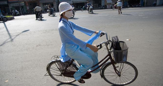 Lady cycling through the streets, Hanoi, Vietnam