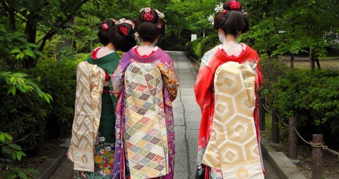 Three-geisha-wearing-kimonos-in-a-traditional-street-of-Kyoto