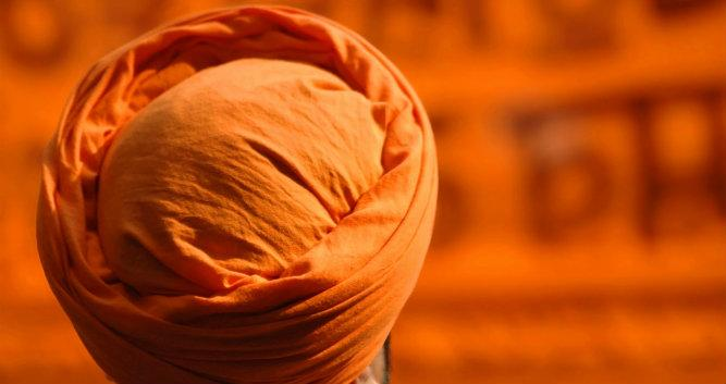 Sikh wearing orange turban, India