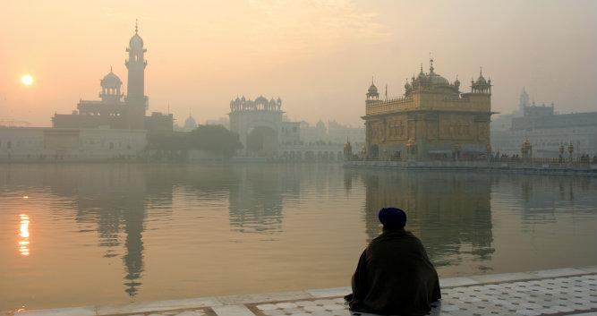 View of the Golden Temple with a men in meditation, Amritsar, India