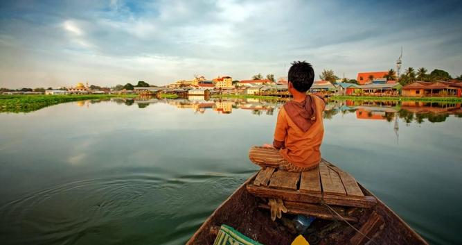Young boy riding a boat on Tonle Sap Lake, Cambodia