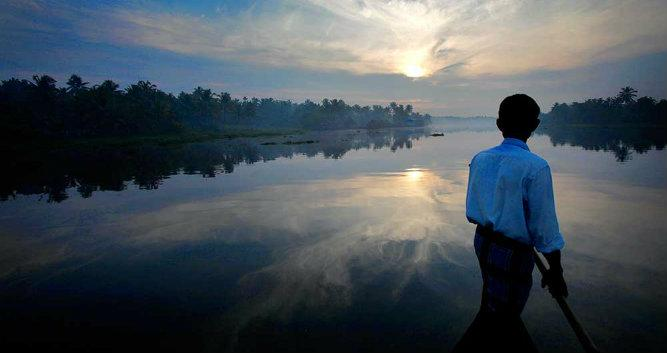 Man looking out to the backwaters, Kerala, India