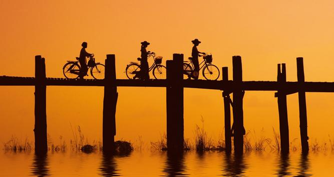 Cyclists at sunset over U Bien bridge, Mandalay, Burma